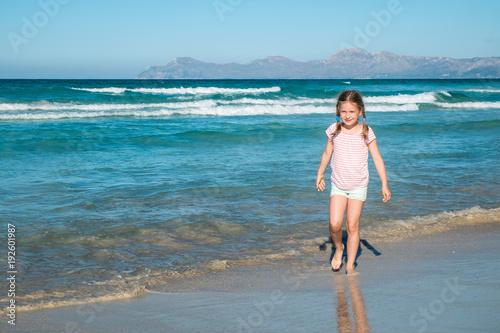Cute girl walking on the beach
