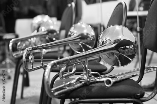 Trombones lying on chairs in black and white tones - Buy