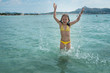 Happy girl in a yellow swimming suit splashing water