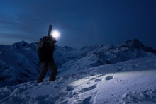 Professional Tourist Commit Climb On Great Snowy Mountain At Night. Wearing Backpack, Headlamp And Ski Wear. Backcountry. Brave Extreme Traveler With A Snowboard Behind His Back Climbs Winter Slope