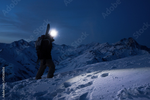 Obraz Professional tourist commit climb on great snowy mountain at night. Wearing backpack, headlamp and ski wear. Backcountry. Brave extreme traveler with a snowboard behind his back climbs winter slope - fototapety do salonu