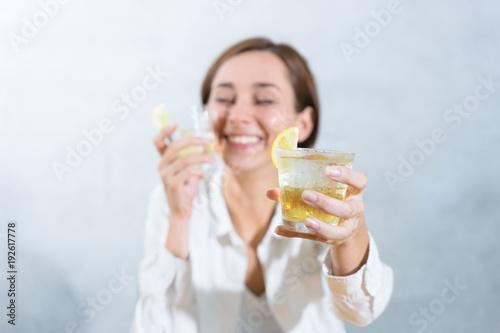 Fotografía  レモンを添えた冷たい飲み物を渡す女性