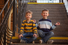 Little Two Boys Sitting On Stairway In Sunny Day.