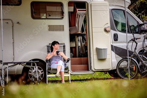 In de dag Kamperen Woman is standing with a mug of coffee near the camper RV.