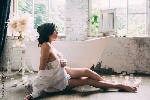 Fotografie, Obraz A beautiful boudoir morning of the bride, a pretty girl in a white man's shirt a