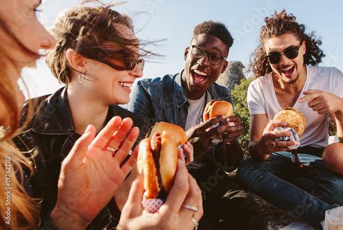 Foto op Canvas Kruidenierswinkel Group of friends eating burger on mountain top