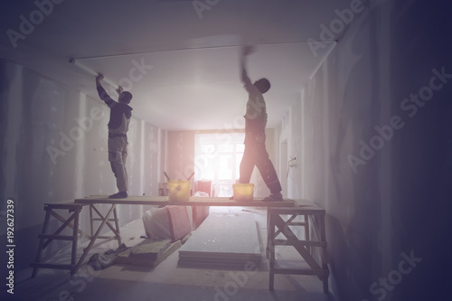 Fotografie, Obraz  Workers are installing ceiling from wooden platform in apartment is under construction, remodeling, renovation, and reconstruction