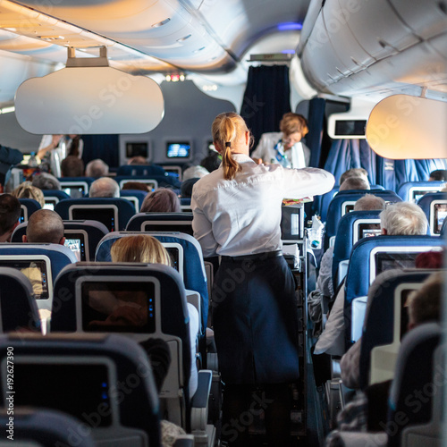 Tuinposter Interior of large commercial airplane with flight attandants serving passengers on seats during flight. Stewardesses in dark blue uniform walking the aisle. Horizontal composition.