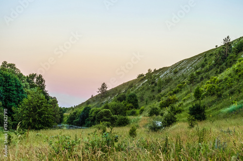 Green chalk hills in evening time. The archaeological monument - Krapivenskoye ancient settlement, Belgorod region, Russia.