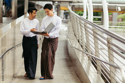 Myanmar peoples walk and talking business using folder in city Canvas Print