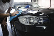 A man cleaning car with microfiber cloth, car detailing (or valeting) concept. Selective focus.