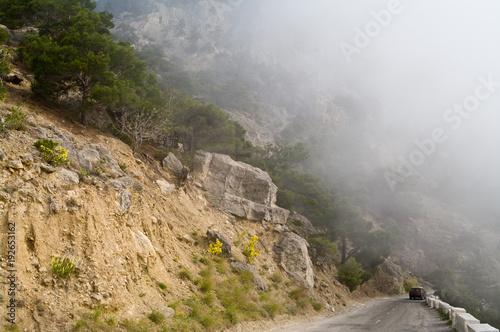 Fototapeta Dangerous winding road in the mountains in a fog