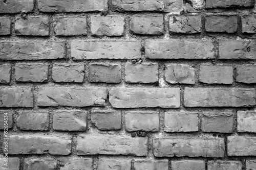 Fotografering  Old deteriorated brick wall texture background in black and white with vignetting