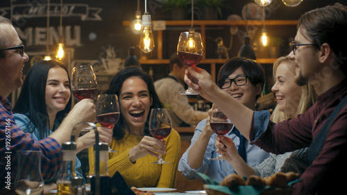 Diverse Group of Friends Celebrate with a Toast and Clink Raised Wine Glasses in Celebration. Beautiful Young People Have Fun in the Stylish Bar/ Restaurant.