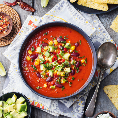 Mexican tomato, bean, bell pepper soup in black bowl. Top view