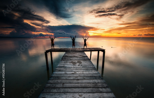 silhouette of 3 unknown children on wooden jetty during sunset. image contain soft focus due to water or subject movement.