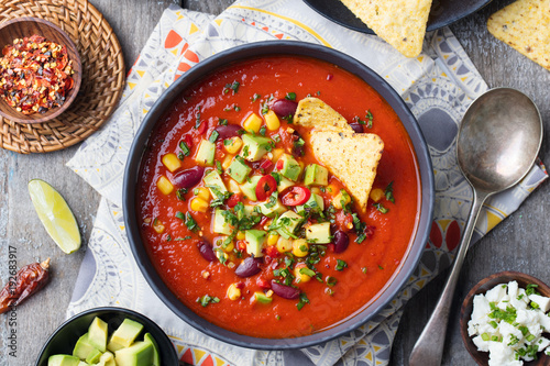 Mexican tomato, bean, bell pepper soup in bowl.