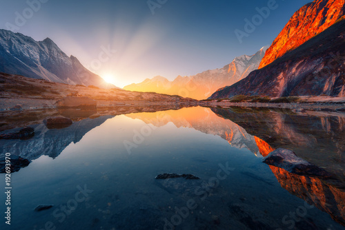 Deurstickers Bergen Beautiful landscape with high mountains with illuminated peaks, stones in mountain lake, reflection, blue sky and yellow sunlight in sunrise. Nepal. Amazing scene with Himalayan mountains. Himalayas