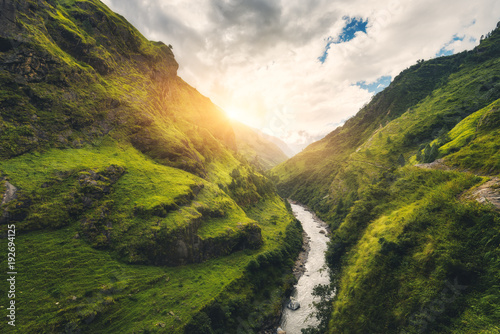 Foto auf Gartenposter Gebirge View with amazing mountains covered green grass, river, meadows and forest, blue sky with clouds, sun in autumn in Nepal at sunset. Mountain valley at bright sunny evening. Travel in Himalayas. Nature