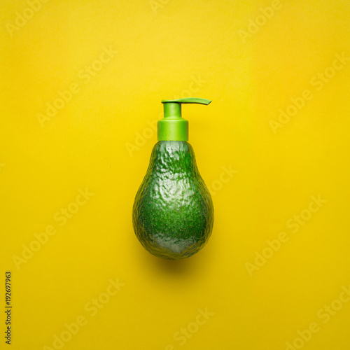 Natural beauty / Creative concept photo of avocado with cream dispenser on yellow background.