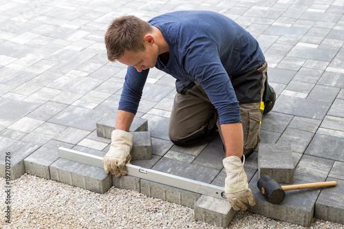 Handwerker verlegt Pflastersteine