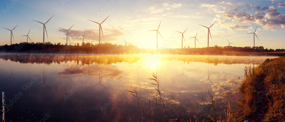 Fototapety, obrazy: Windmills for electric power production on the field. wonderful sunny sunrise on lake.