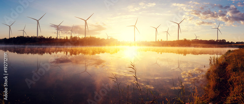 Windmills for electric power production on the field. wonderful sunny sunrise on lake.