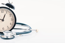 Regular Or Routine Medical Examination Concept, Stethoscope And Alarm Clock On White Background