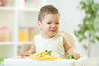 funny baby boy eating healthy food in nursery