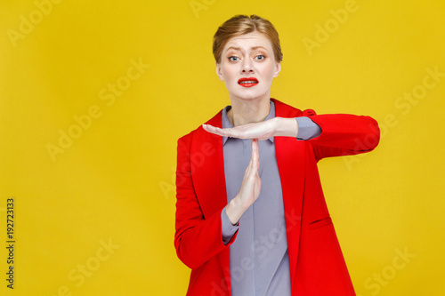 Time out! Unhappy business woman in red suit showing pause sign. Canvas Print