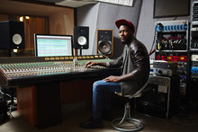 Young African-american Rapper In Baseball Cap, Jeans And Leather Jacket Working By Switchboard In Studio