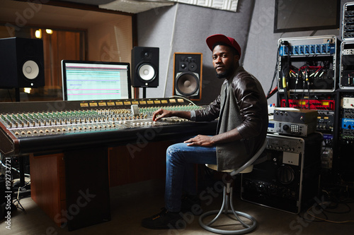 Young African-american rapper in baseball cap, jeans and leather jacket working by switchboard in studio - 192732721
