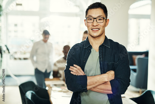 Photo  Smiling young Asian designer with colleagues working in the background