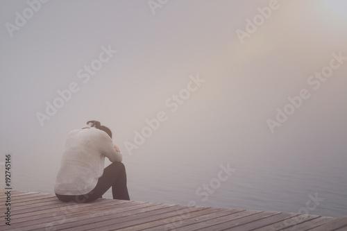 Photo  Anonyme traurige Frau sitzt auf einem Steg im Nebel