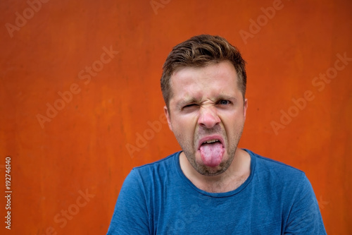 A young man with a grimace of disgust on his face Wallpaper Mural