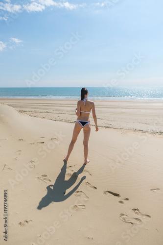 Fotografía  Unrecognizable woman in bikini walks down the beach along the seashore leave footprints on the sand