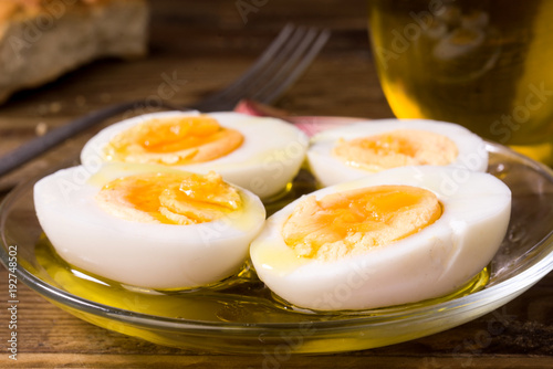 Fotografía  hard boiled eggs cut in half with oil and vinegar, on wooden board