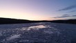 Gliding aerial shot of frozen river at dawn during winter