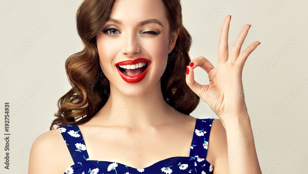 Fototapeta Pin-up retro girl with curly hair  winking, smiling and showing OK sign . Presenting your product. Expressive facial expressions