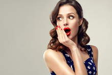 Surprised And Amazed Girl Holds  Her Cheeks And Looks In The Side .  Beautiful Woman With Curly Hair And Red Nails. Expressive Facial Expressions.  Presenting Your Product.