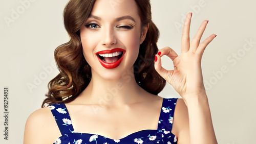 Foto auf Leinwand Pop Art Pin-up retro girl with curly hair winking, smiling and showing OK sign . Presenting your product. Expressive facial expressions