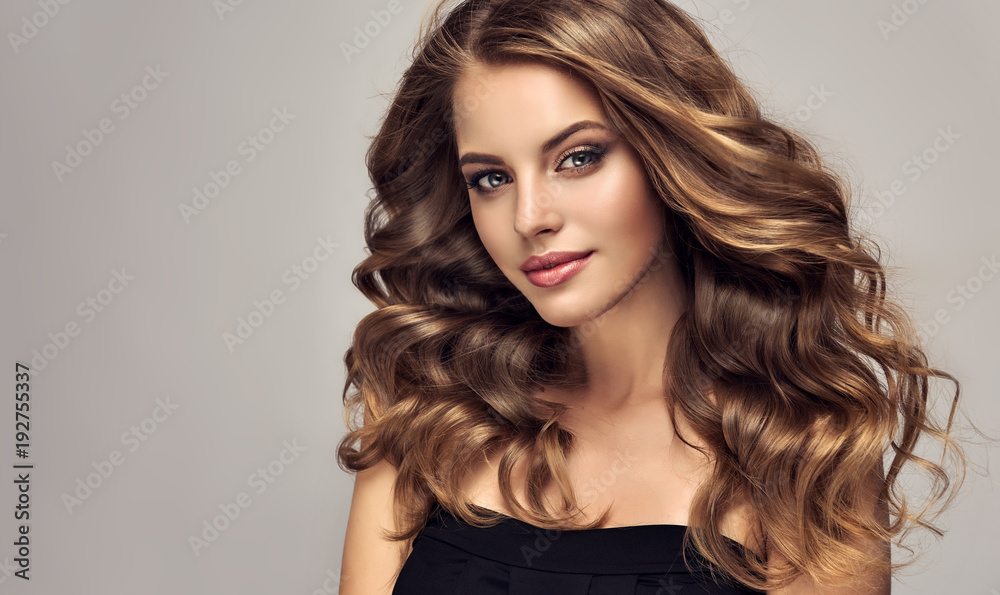 Fototapeta Brunette girl with long and shiny wavy hair . Beautiful model with curly hairstyle .