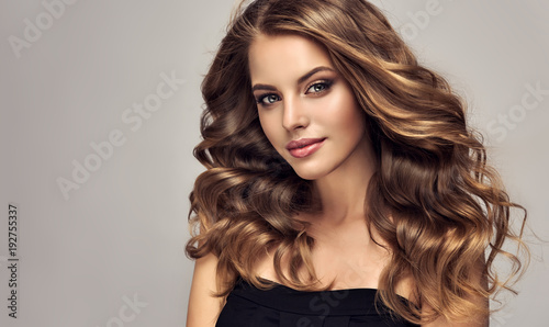 Door stickers Hair Salon Brunette girl with long and shiny wavy hair . Beautiful model with curly hairstyle .