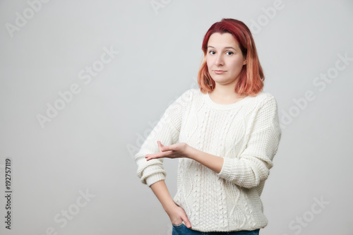Studio shot of irritated confused attractive woman showing left side of copy space with hand and expressing puzzlement, standing over gray background Canvas Print