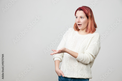 Photo  Studio shot of irritated confused attractive woman showing left side of copy space with hand and expressing puzzlement, standing over gray background