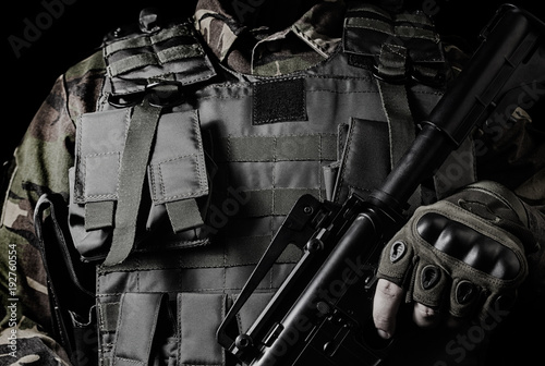 Fotografía  Black and white closeup photo of a soldier in military outfit with weapon on black background