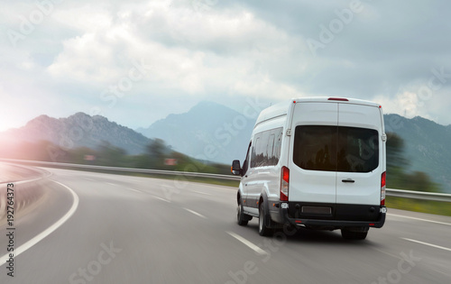 Fotografie, Obraz  passenger bus van accelerating on a background of mountains
