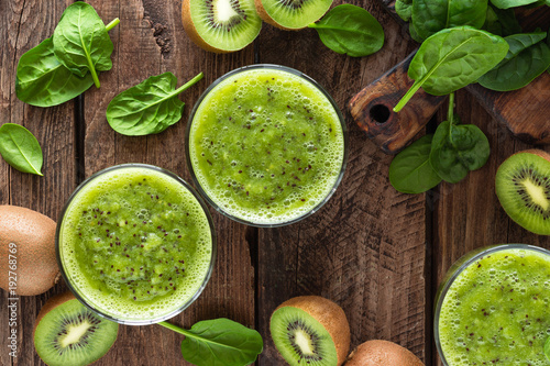 Kiwi smoothie drink of spinach leaves and fresh fruits on wooden rustic table, h Canvas Print
