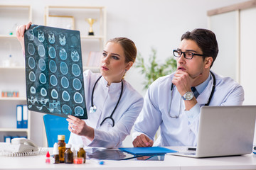 Two doctors examining x-ray images of patient for diagnosis