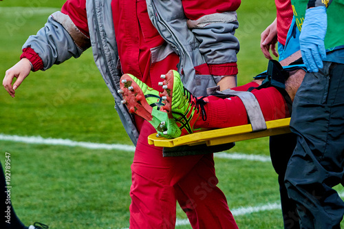 Fotografiet  doctors take away from the field injured player